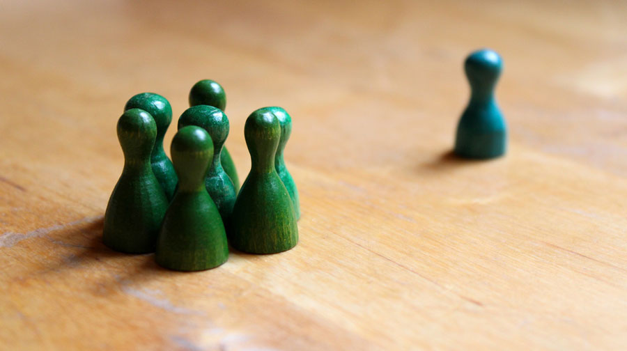 Play figures, several green ones in a group and one blue on the side.
