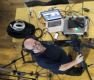 Person smiling at the camera surrounded by technical equipment, videocamera and headphones