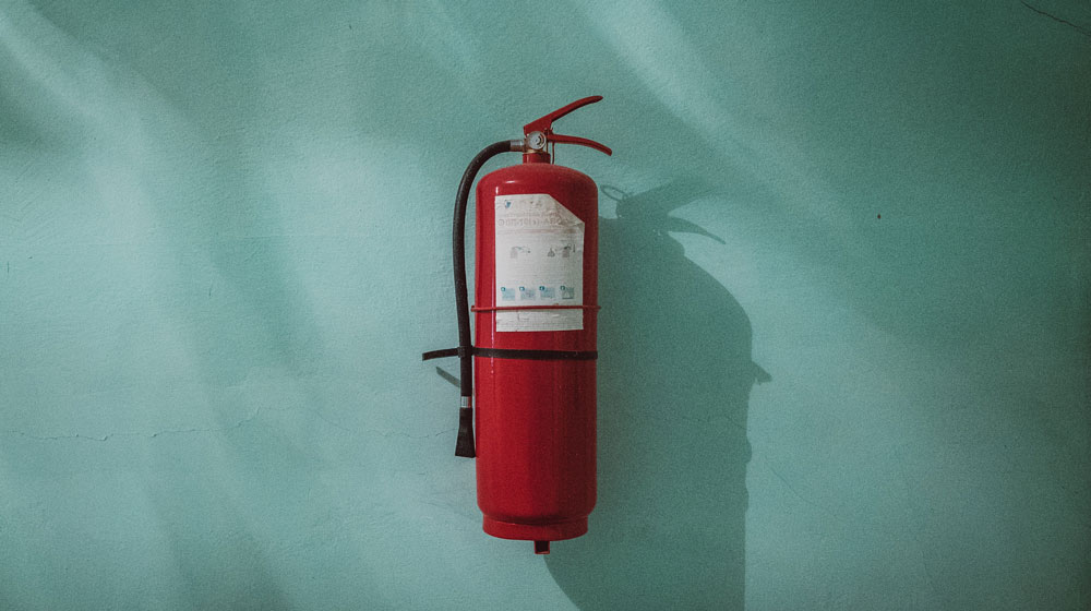 Fire-extinguisher in front of a wall.